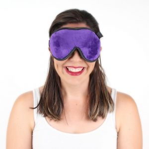 Lady smiling wearing purple sleep mask to bed