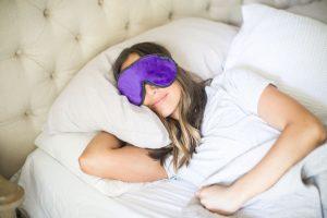 Lady sleeping peacefully in luxury purple plush sleep mask