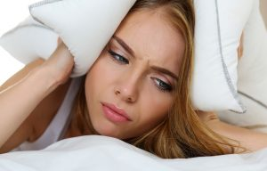 Young beautiful woman lying in bed suffering with insomnia covering head and ears with pillow