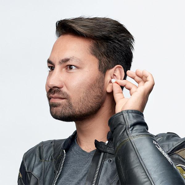 man inserting earplug