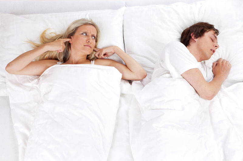 man snoring in bed with lady blocking ears