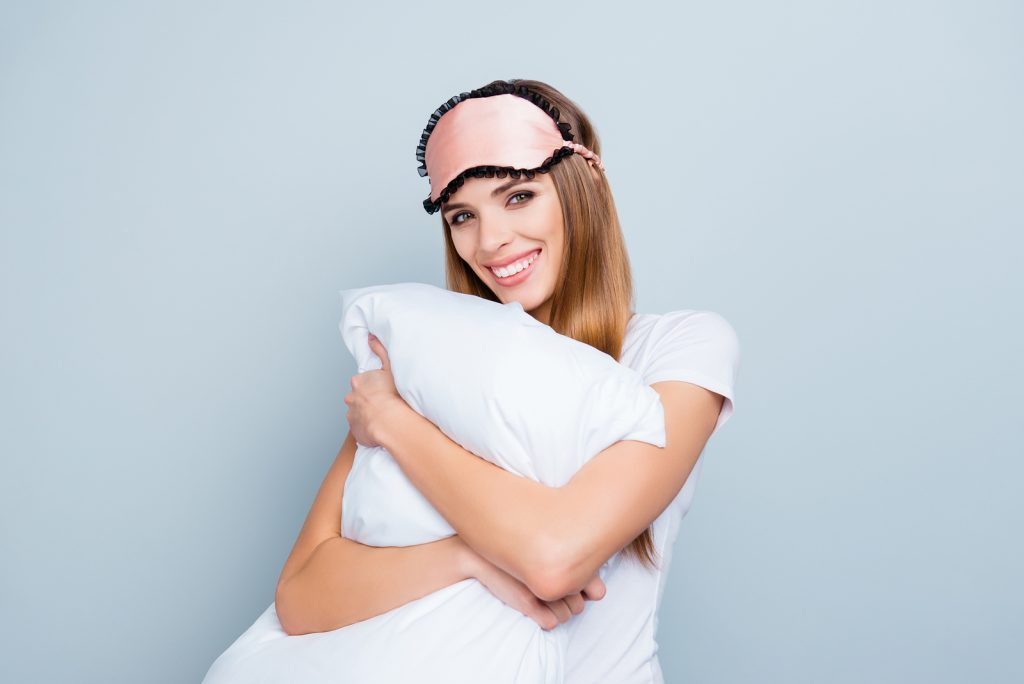 lady hugging pillow with sleep mask