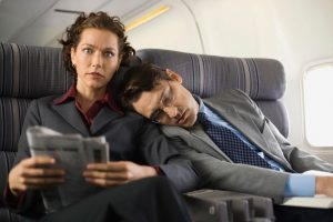 person asleep on other person in plane