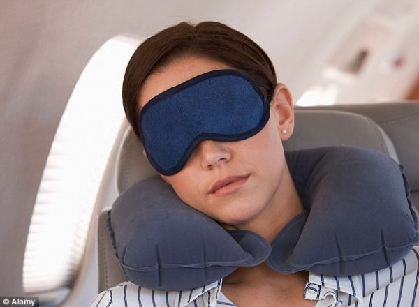 lady wearing sleep mask and blue plush inflatable travel pillow