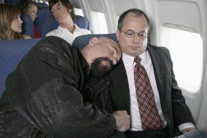 man asleep on other mans shoulder when travelling