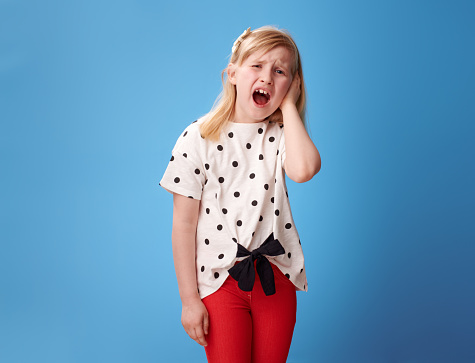 unhappy modern girl in red pants with a earache on blue background Sleep and Sound