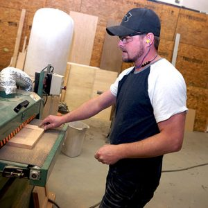 man with electric saw wearing plugfones headphones