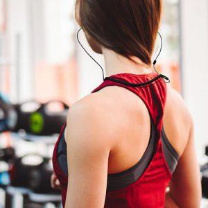 girl wearing plugfones headphones at gym