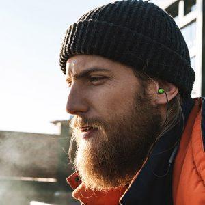 man wearing plugfones headphones at work