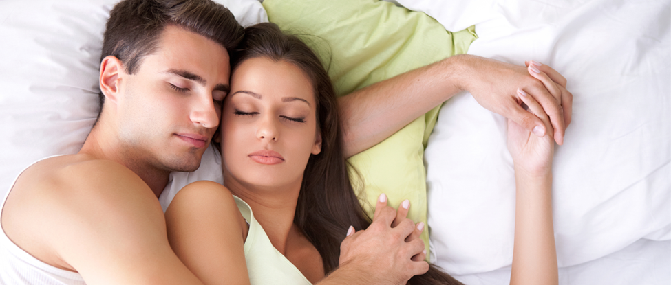 man and lady cuddling in bed